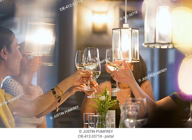 Women friends toasting white wine glasses dining at restaurant table