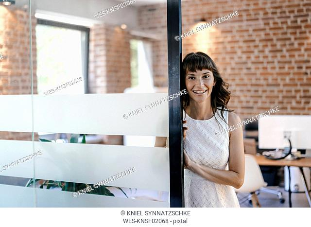 Businesswoman standing in office, holding digital tablet
