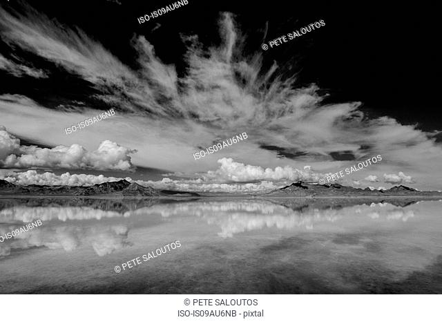 Reflection pool of horizon over water, mountain range and clouds, black and white, Bonneville, Utah, USA