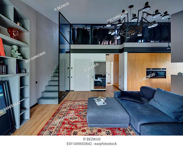 Modern interior with light walls and parquet with red carpet on the floor. There is blue sofa with pillows, mirror, door, shelves with decorations and books