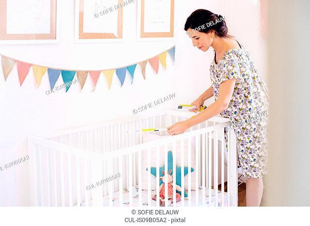 Pregnant mid adult woman measuring crib in childs nursery