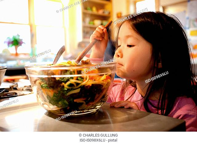 Girl mixing salad in salad bowl
