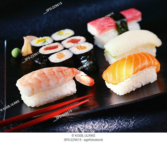 Sushi on brown platter with chopsticks