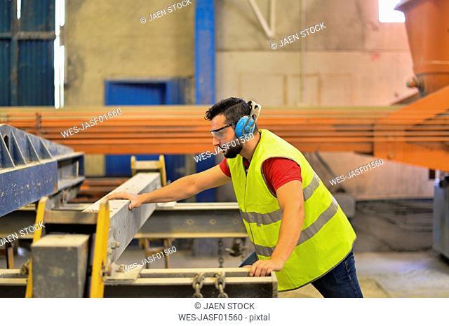 Worker in concrete factory cutting steel, wearing ear defenders
