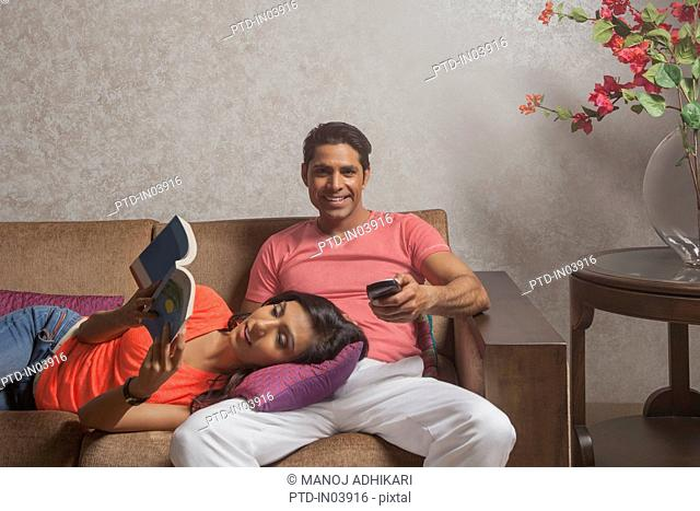 India, Man watching television and woman reading book on sofa