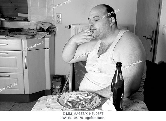 man in undershirt sitting in the kitchen with cigarette, french fries and beer, Ruhr Area