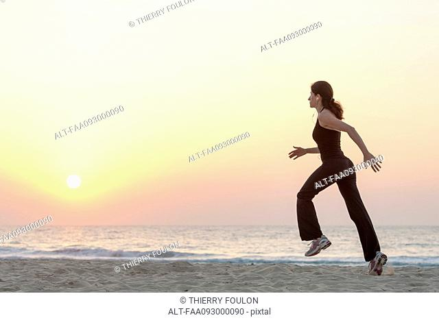 Woman jogging on beach at sunrise with earphones, side view