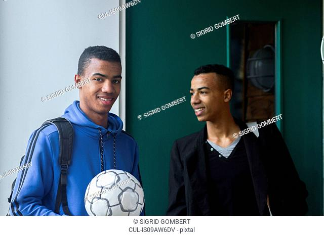 Twin brothers standing in doorway, holding football