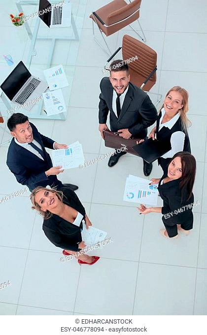 view from the top.business team discussing marketing charts,standing in the office.business concept