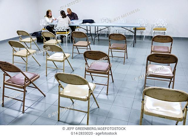 Florida, Miami Beach, condominium board, meeting, table, Black, Hispanic, man, woman, counting ballots, papers, folding chairs, empty, annual election, votes