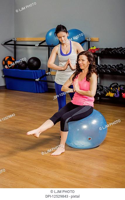 An attractive middle-aged women working out doing yoga poses on a balance ball at the gym with her personal trainer giving assistance; Spruce Grove, Alberta