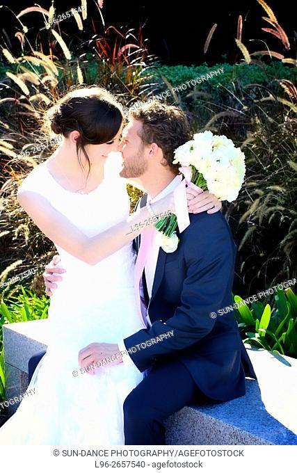 happy bride & groom sitting & embracing in park