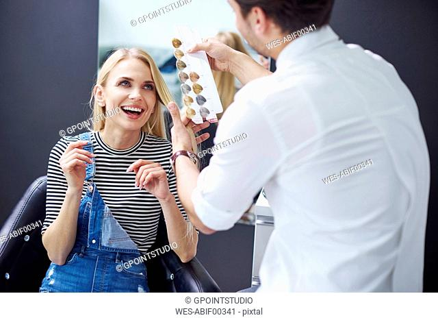 Hairdresser and happy woman at hair salon