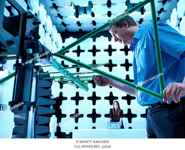 Engineers checking a bilog antenna for electromagnetic compatibility (EMC) radiated immunity testing in a semi anechoic chamber relative to the electronic...