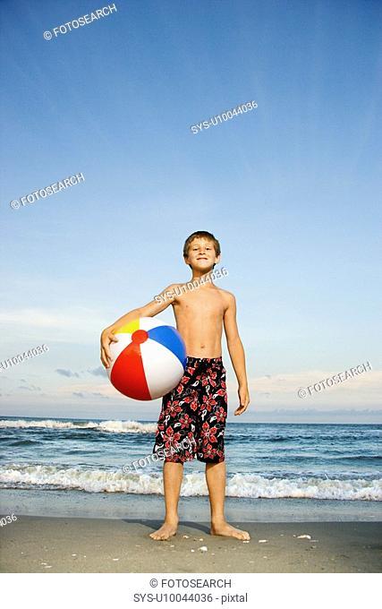 Caucasian pre-teen boy holding beach ball on beach