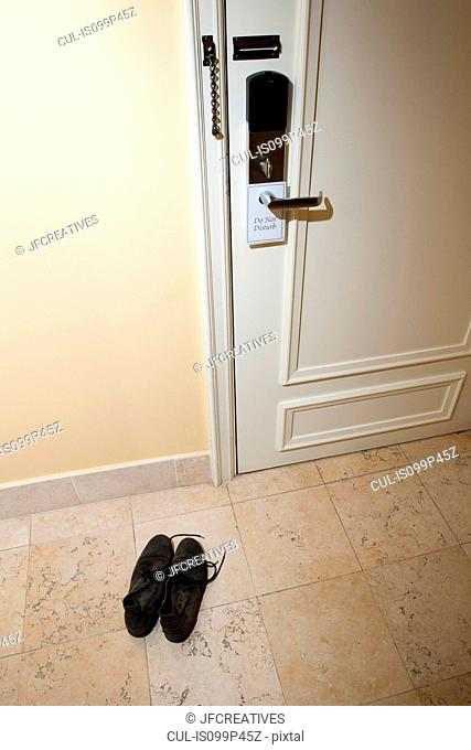 Pair of shoes by hotel room door