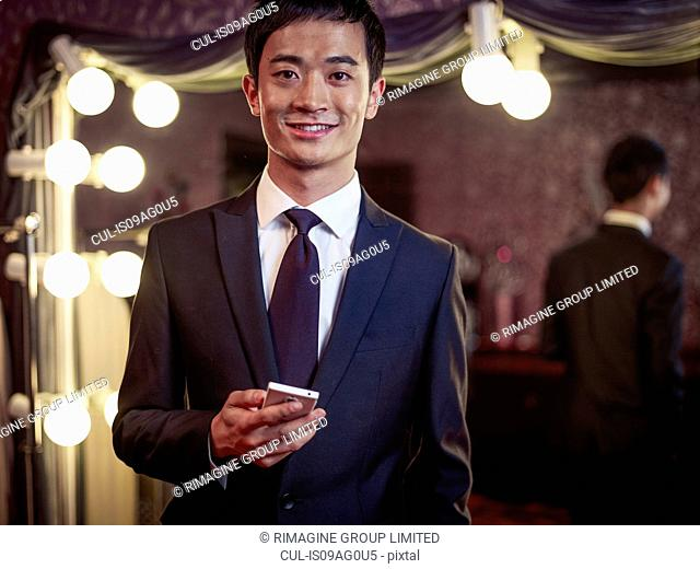 Portrait of young man in new suit in traditional tailors shop