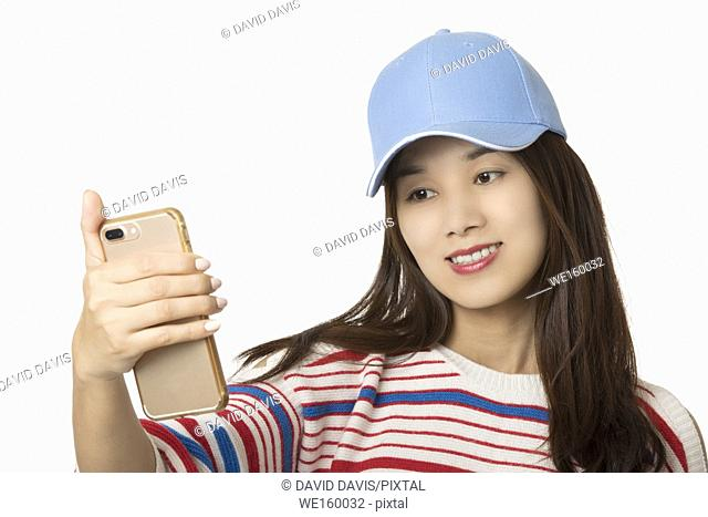 Asian American woman using a smartphone to take a selfie isolated on a white background