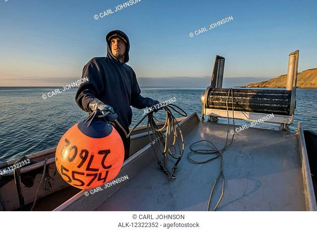 Commercial fishing boat crewman prepares to toss a buoy into the waters of Bristol Bay, Southwest Alaska, USA