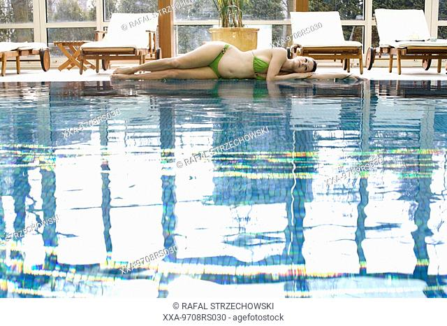 preganant woman relaxing by swimming pool