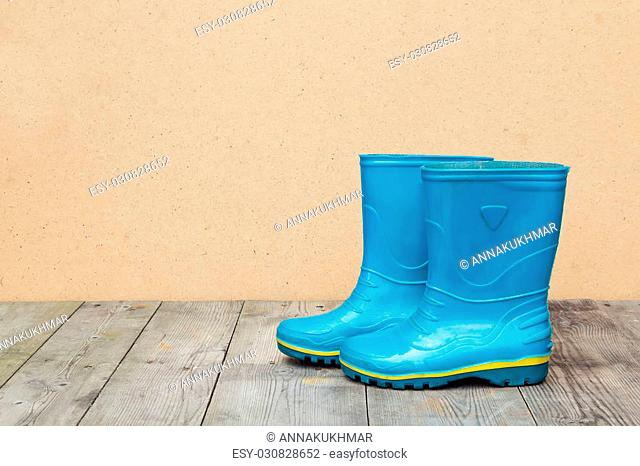 Blue rubber boots on a wooden floor. Autumn season concept