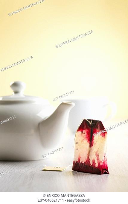 white teapot on table with cup and tea bag