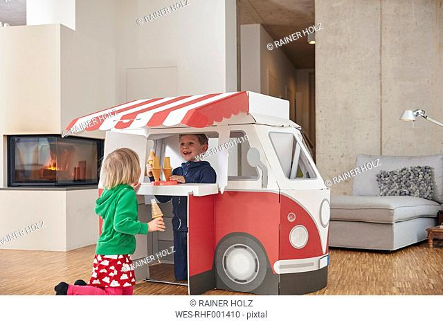 Brother and sister with popsicles and model ice cream van in living room