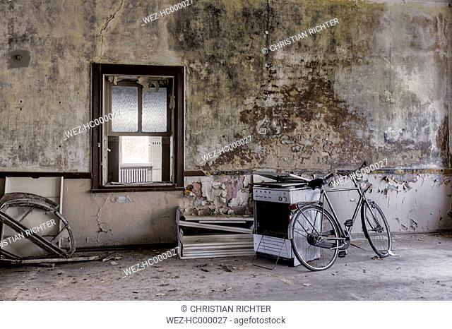 Germany, Thuringia, Erfurt, old bike and stove in abandoned room