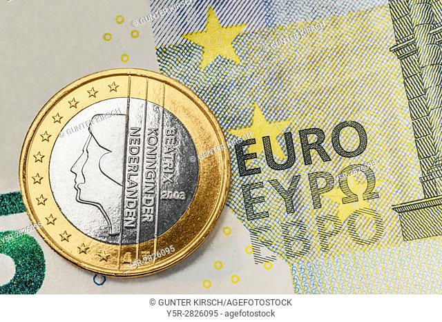 a 1 euro coin from the Netherlands on a 5 euro banknote