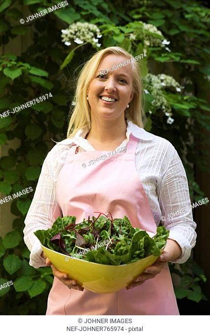 Woman holding a bowl of salad, Sweden
