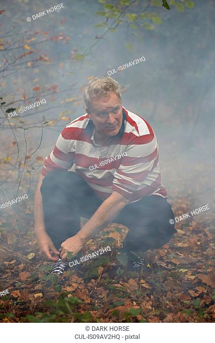 Mature male runner crouching to tie trainer laces in misty forest