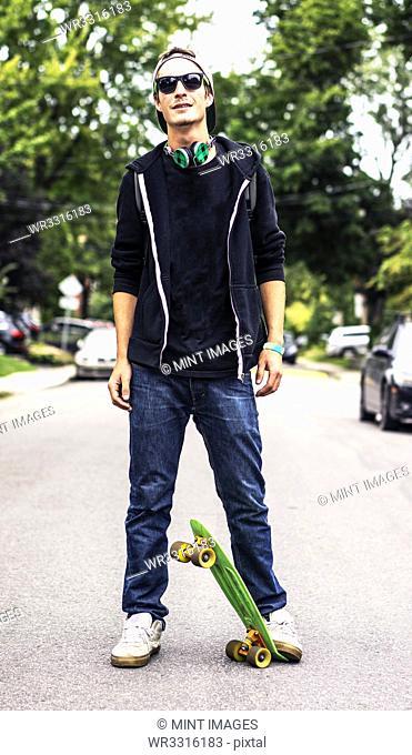Caucasian man with headphones standing on skateboard