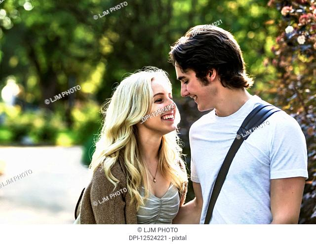 A young couple shares a romantic moment together contemplating a kiss while walking through a university campus; Edmonton, Alberta, Canada