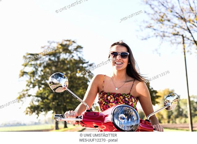 Happy young woman riding motor scooter on country road