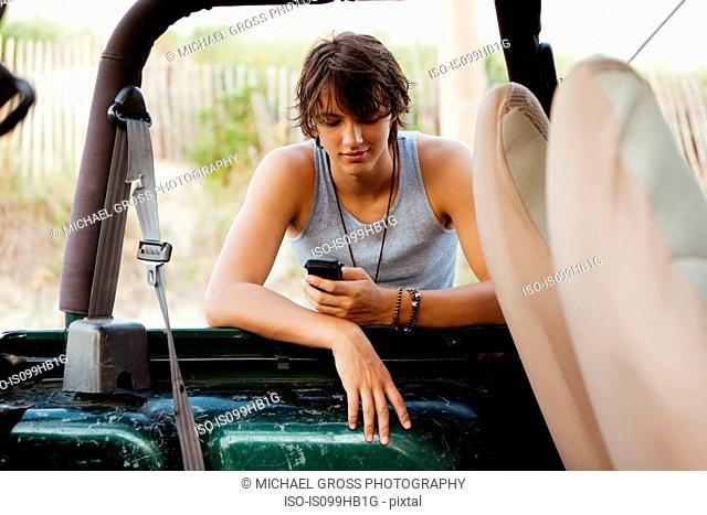 Teenager leaning against jeep checking phone