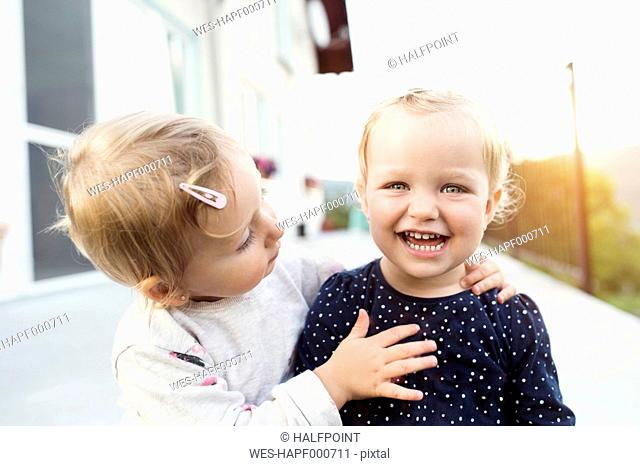 Little girl watching her laughing sister