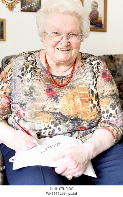 Smiling old woman with glasses writing