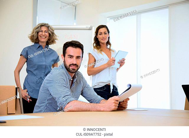 Portrait of young male businessman and two female colleagues in office