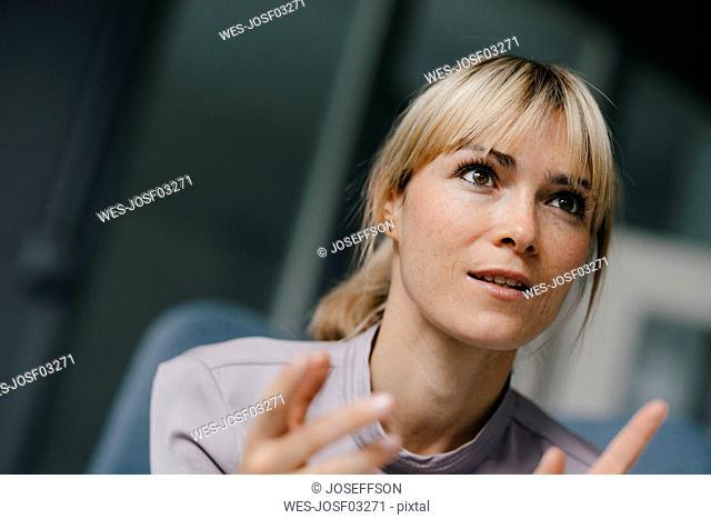 Portrait of a blond businesswoman, talking passionately