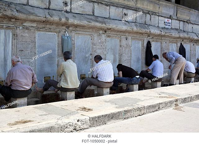 Muslim men wash their feet before praying in The New Mosque, Istanbul, Turkey