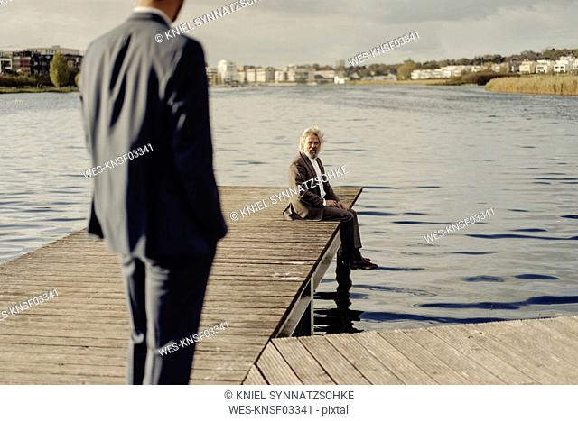 Senior man sitting on jetty at a lake with man in foreground