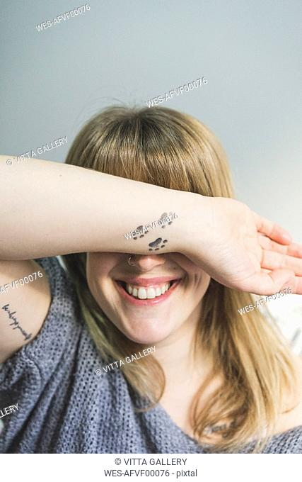 Laughing tattooed woman covering eyes with her arm