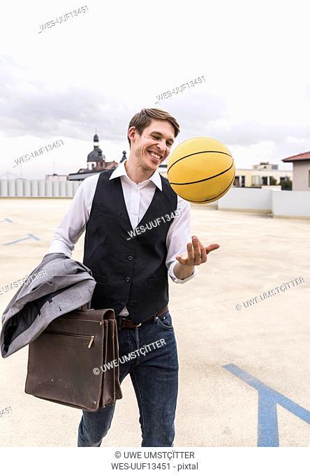 Happy businessman with basketball walking at parking garage