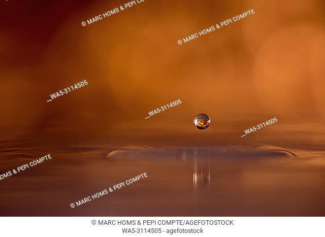 Copper colored water drop suspended above the surface of the water
