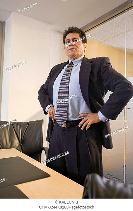 Portrait of Hispanic businessman sitting by table with hand on hip in boardroom