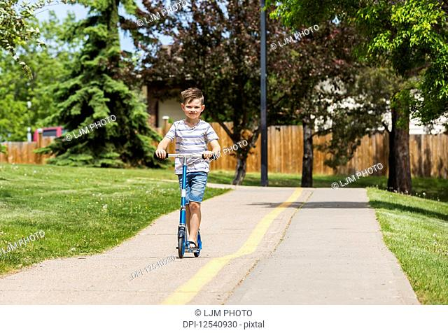 Young boy riding his scooter on a path in a city park and smiling for the camera: Edmonton, Alberta, Canada