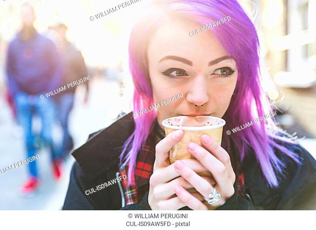 Woman holding coffee cup to mouth