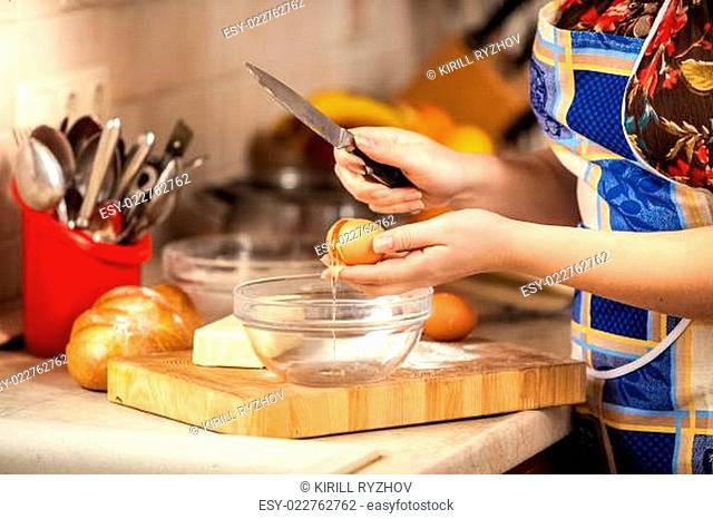 photo of woman cracking egg with knife