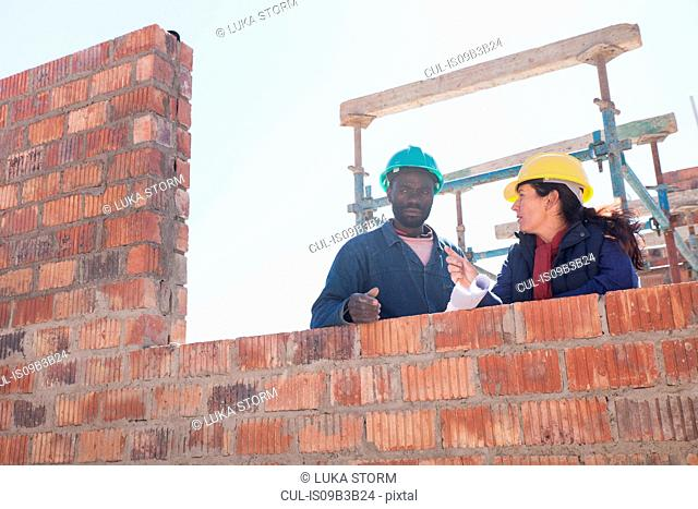 Woman and builder talking on construction site
