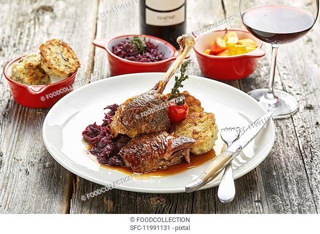 Roast goose with bread dumplings, red cabbage, pumpkin and a glass of red wine